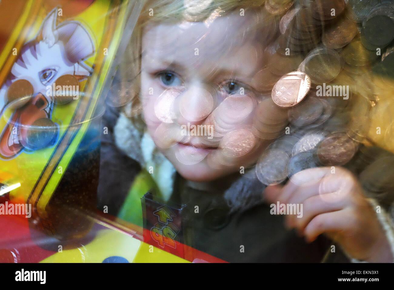 Small girl with amusement arcade machine. - Stock Image