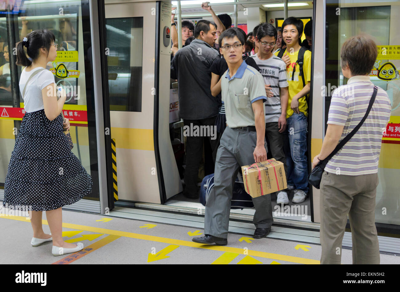 Passengers get off a metro train in Guangzhou, China. Screen doors can clearly be seen between the platform train Stock Photo