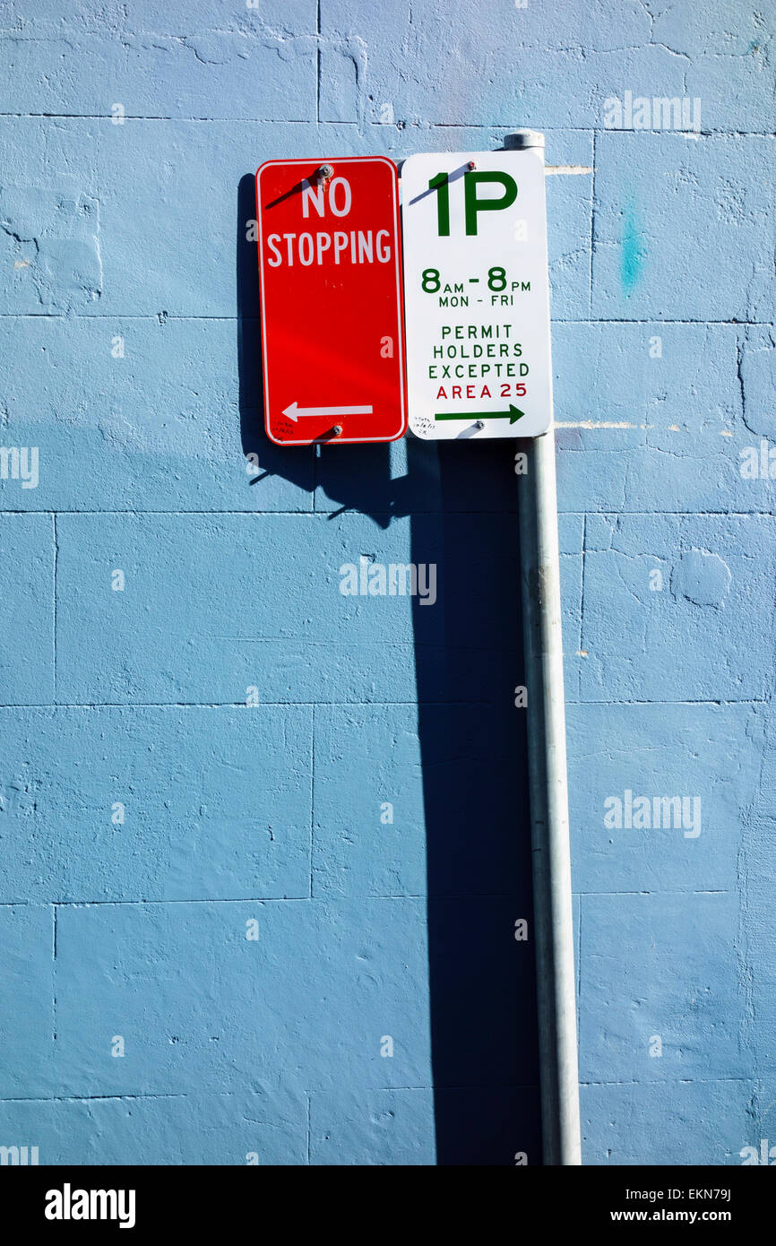 Parking signs - no stopping, limited parking sign against a blue wall. Parking restrictions; no parking; regulations; - Stock Image