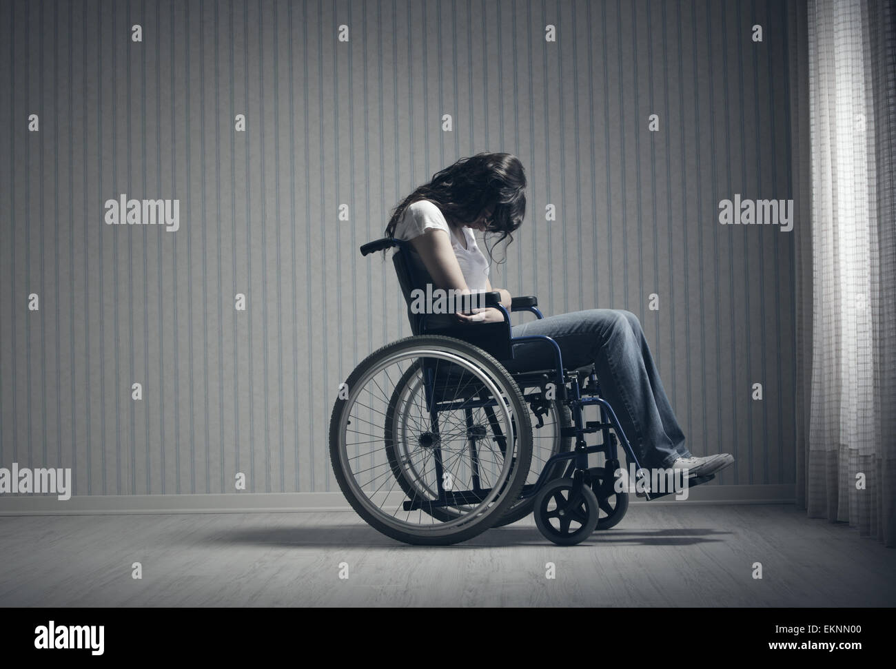 Crying woman sitting in wheelchair - Stock Image