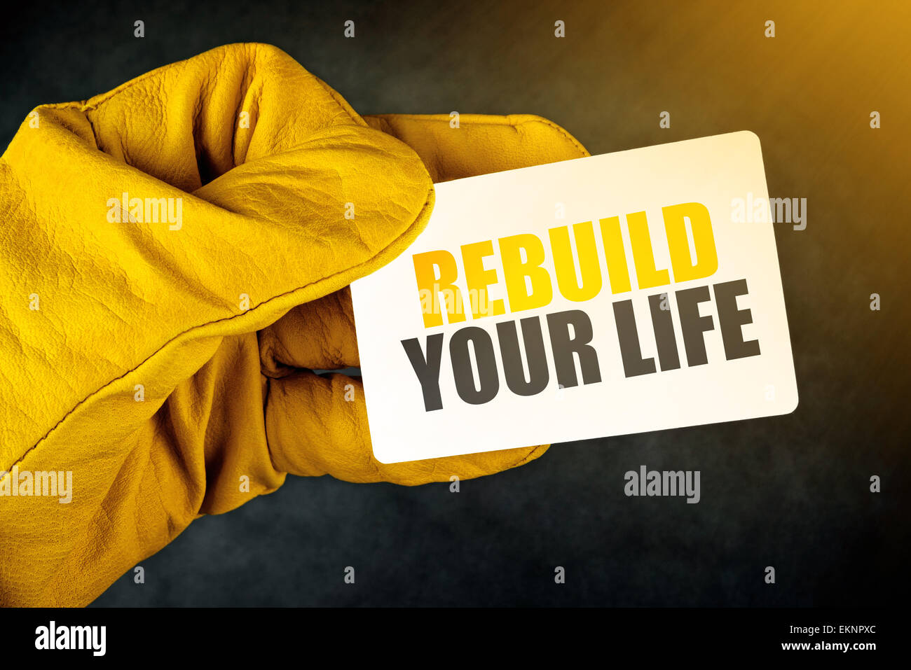 Rebuild Your Life on Business Card, Male Hand in Yellow Leather Construction Working Protective Gloves Holding Card - Stock Image