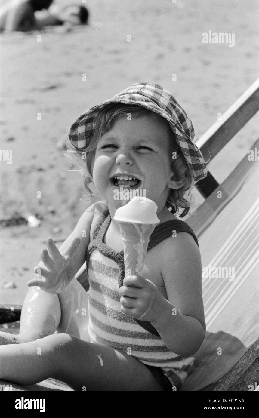 Eighteen month old Nicola England from Bromley, Kent enjoys an ice cream on the beach at Southend On Sea on hot - Stock Image