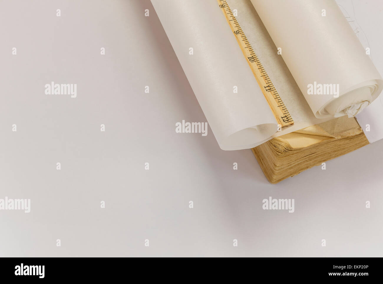 Ruler, tracing paper roll and old book - Stock Image