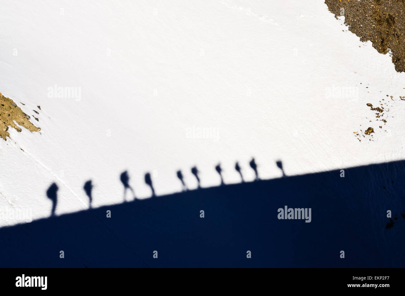 Shadows of group of mountain trekkers on a snow - Stock Image