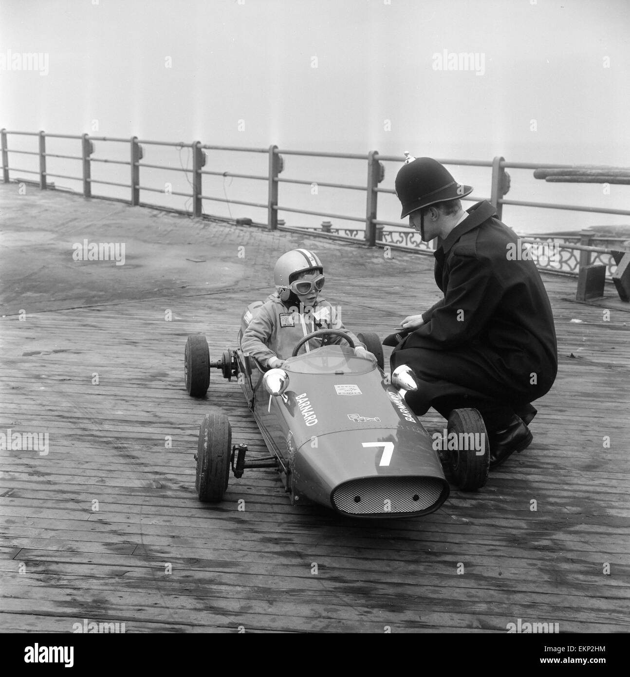 Eight year old Thomas Barnard in his racing car, speaking to a policeman on the West Pier in Brighton ahead of the - Stock Image