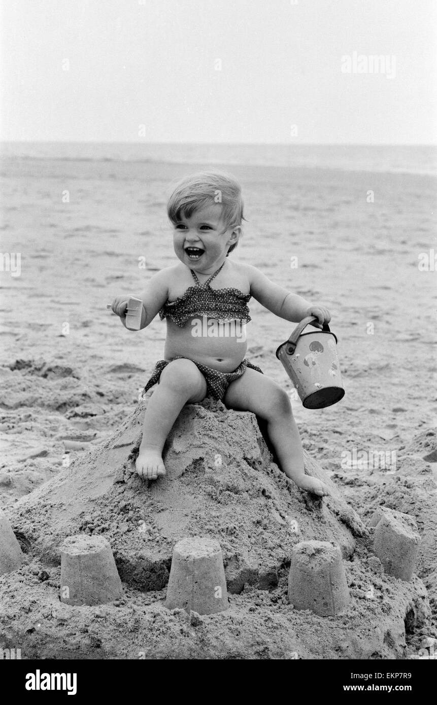 Seventeen month old Sarah Jukes from Wimbledon plays in the sand during a day on the beach on the South coast on - Stock Image