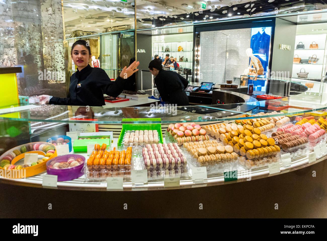 Paris, France. Woman Clerk Waving in French Chocolatier, Macaroons, Pastries Store 'Pierre herme'  in Department - Stock Image