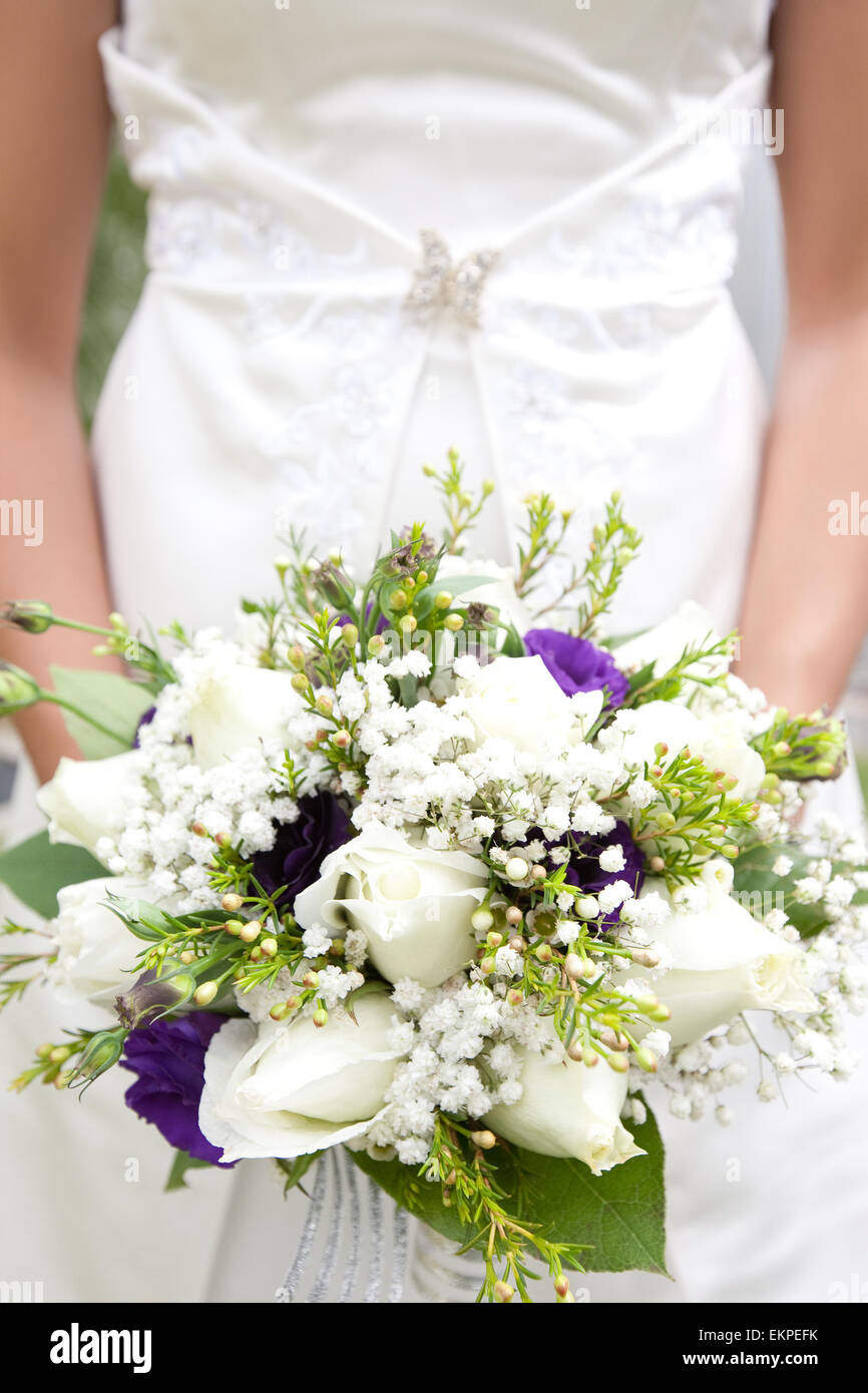 Closeup of bridal bouquet of white roses , baby\'s breath and purple ...