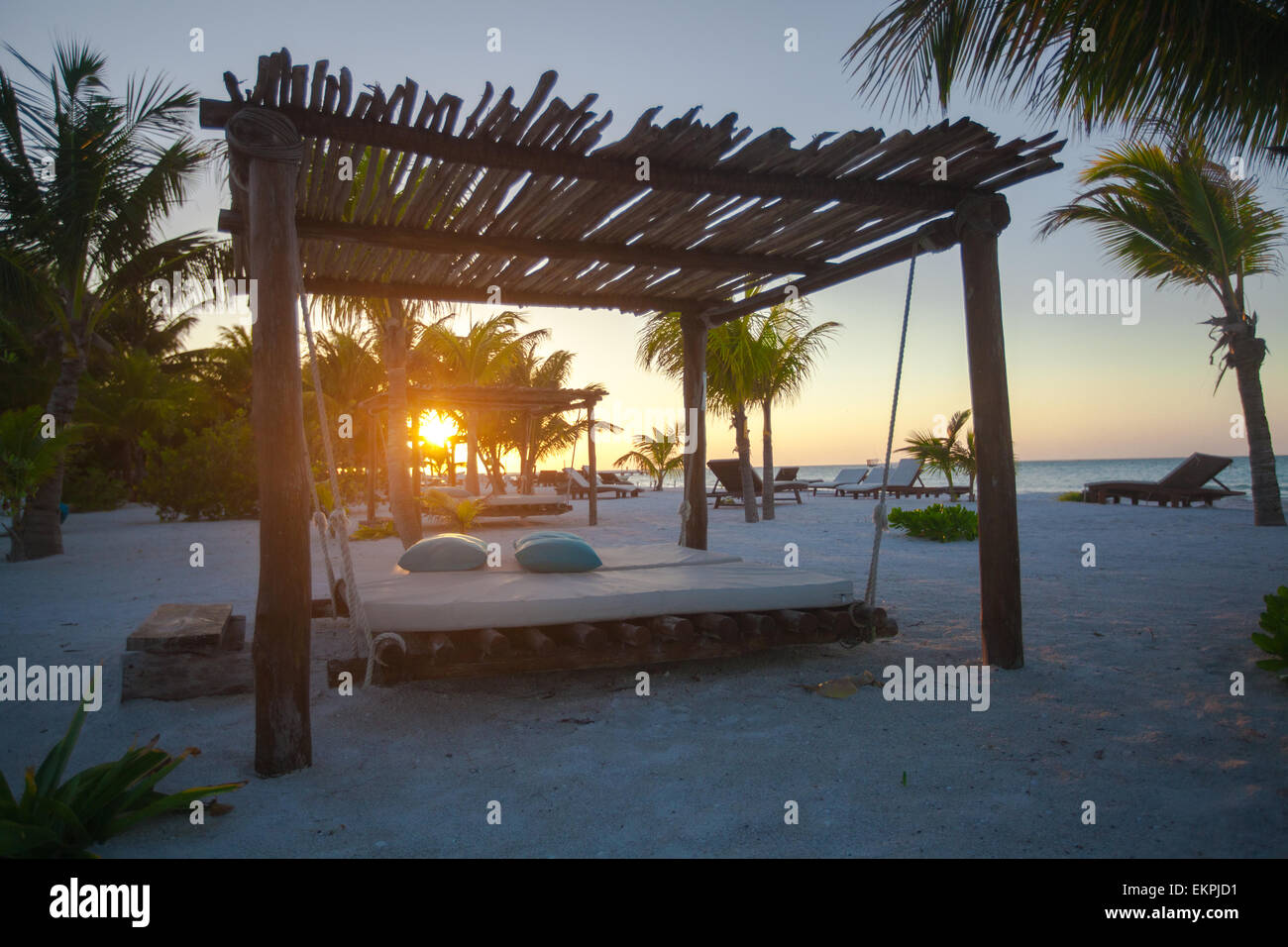 eb680d553ce58 Beach beds among palm trees at perfect tropical coast at sunset ...