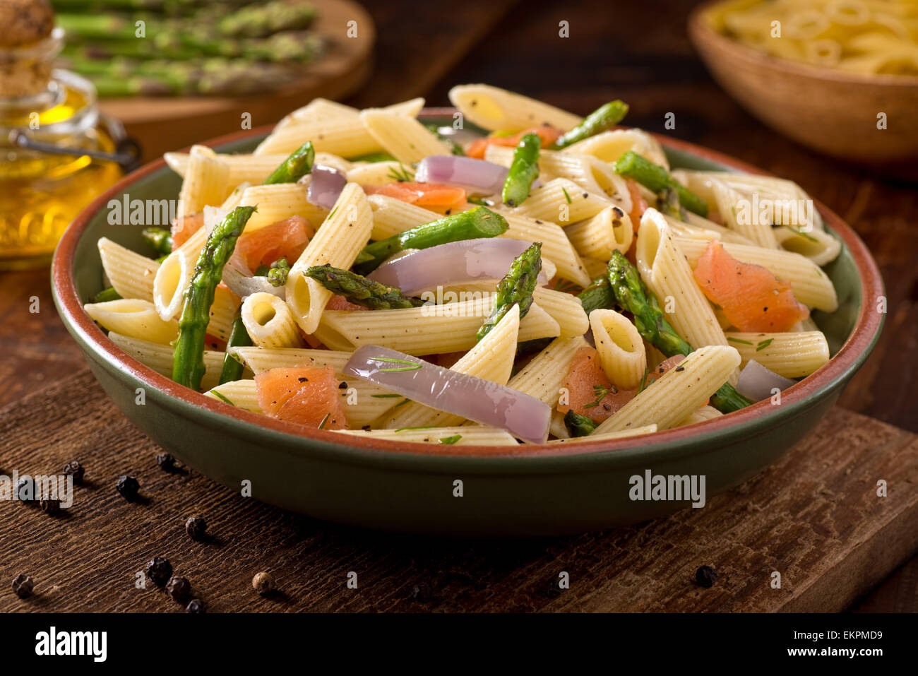 A delicious smoked salmon pasta with penne, asparagus, crushed black pepper, olive oil, and dill. - Stock Image