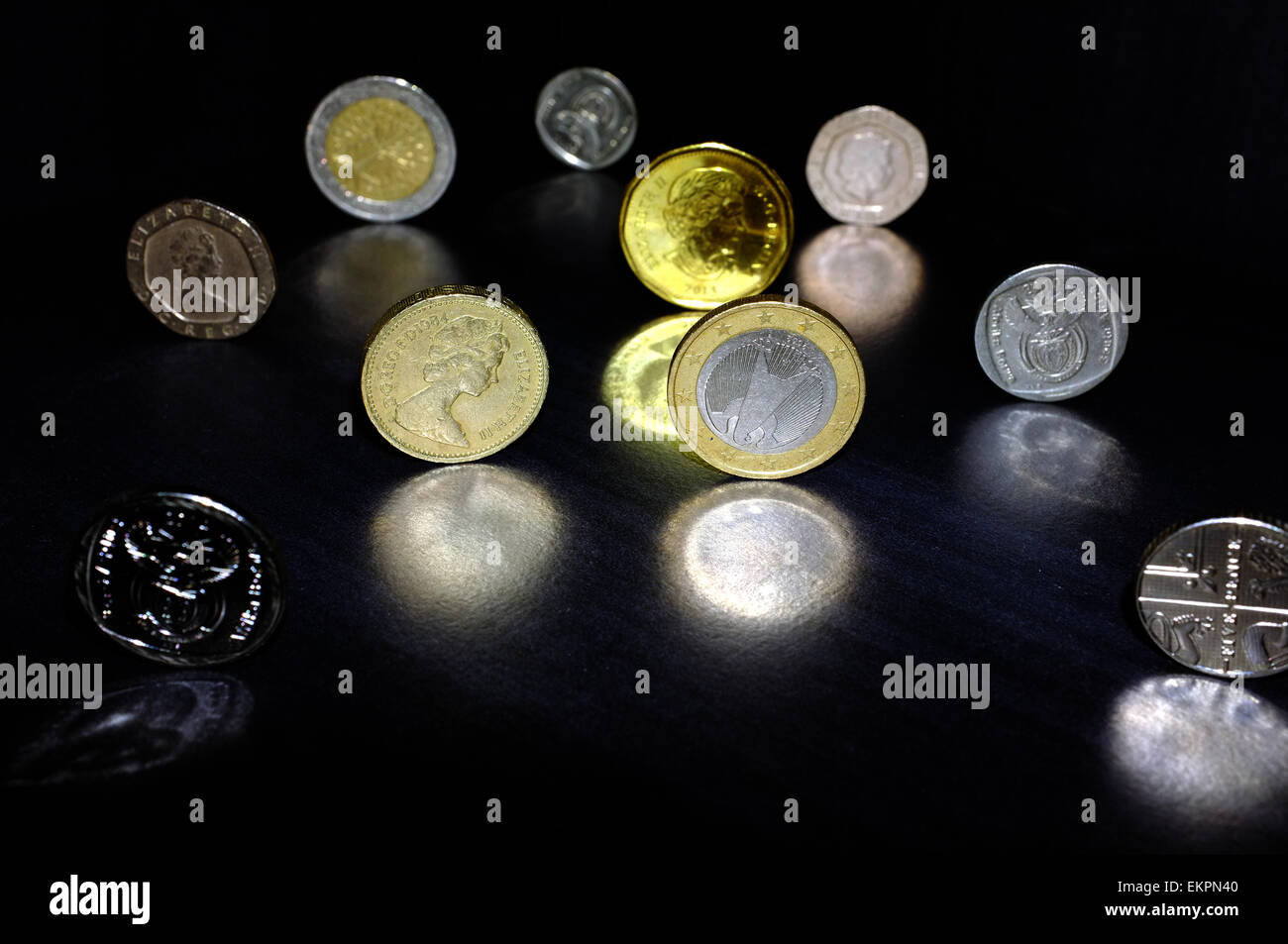 Coins from different currencies reflected on a black surface. - Stock Image