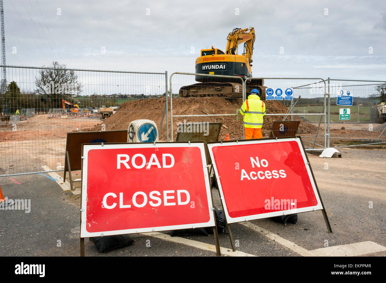 Road closed sign with road works and construction workers building a new road, England, UK - Stock Image