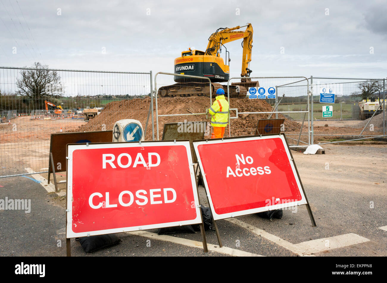 Road closed sign and construction workers building a new road, England, UK - Stock Image
