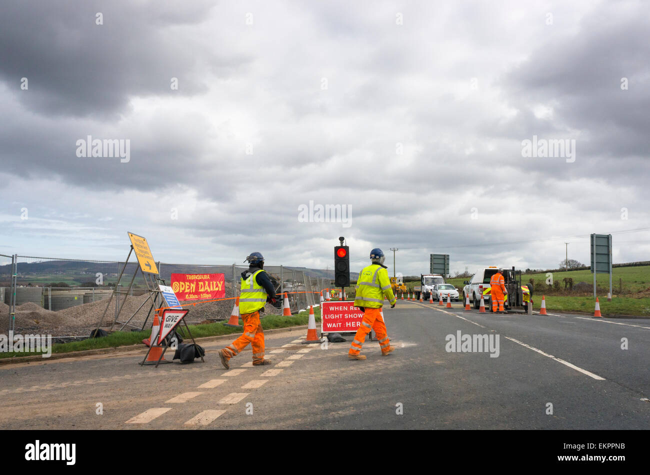Roadworks and workers on a country road with stop lights, England, UK - Stock Image