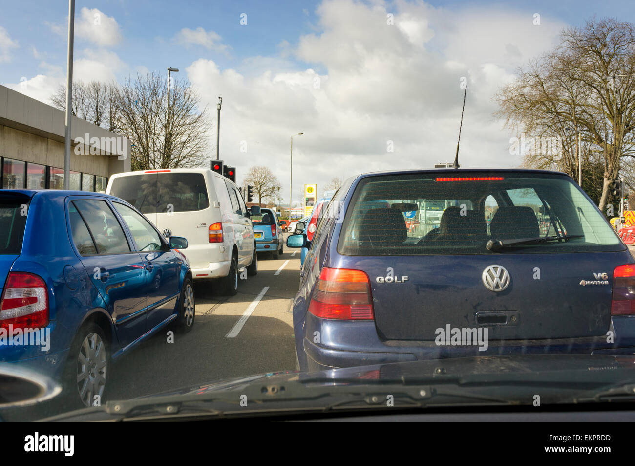 Traffic jam of cars queuing at traffic lights with roadworks in a city, England, UK - Stock Image