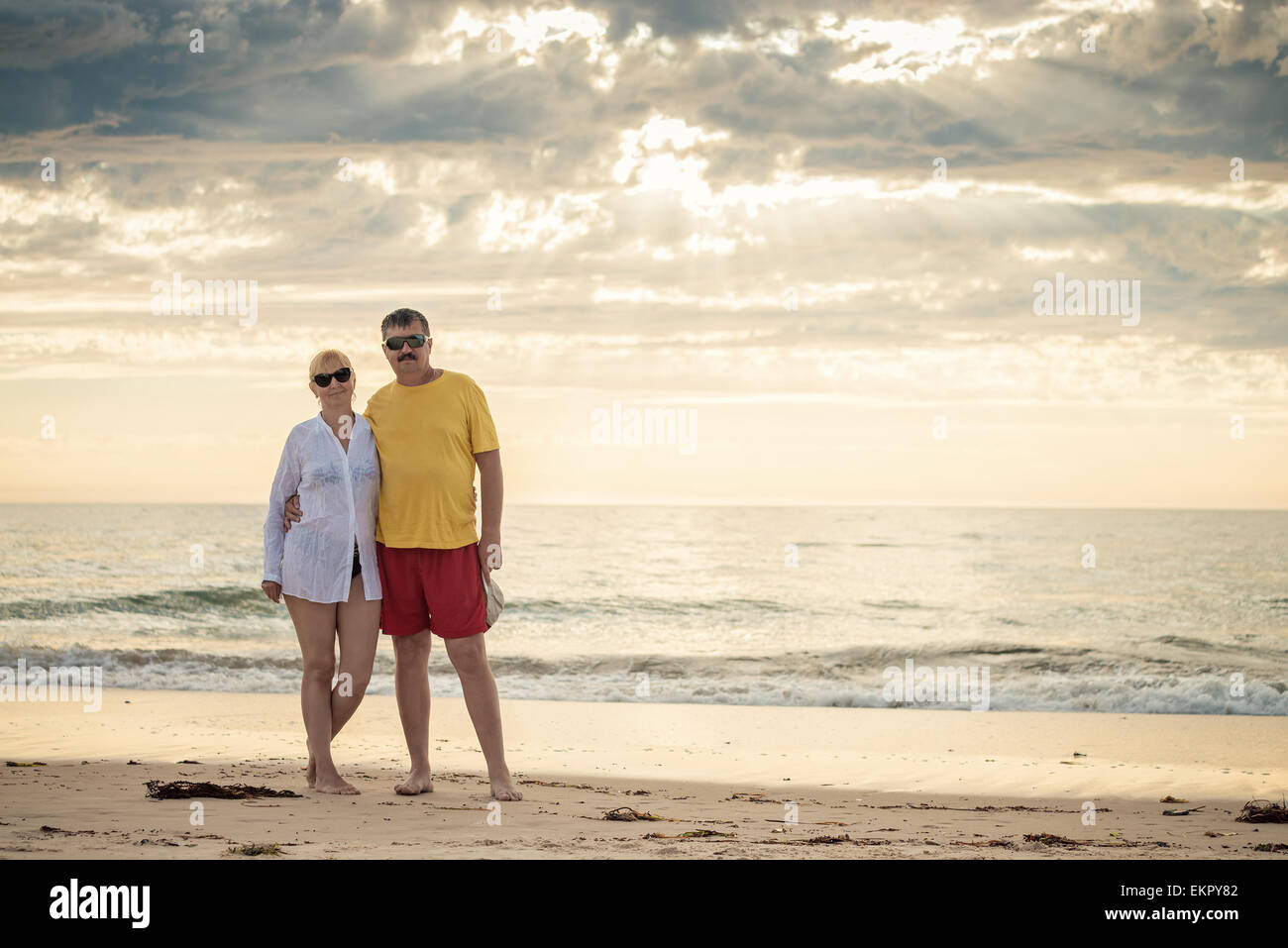 Happy mature couple in mid fifties at the beach. Warm color toning and natural light - Stock Image