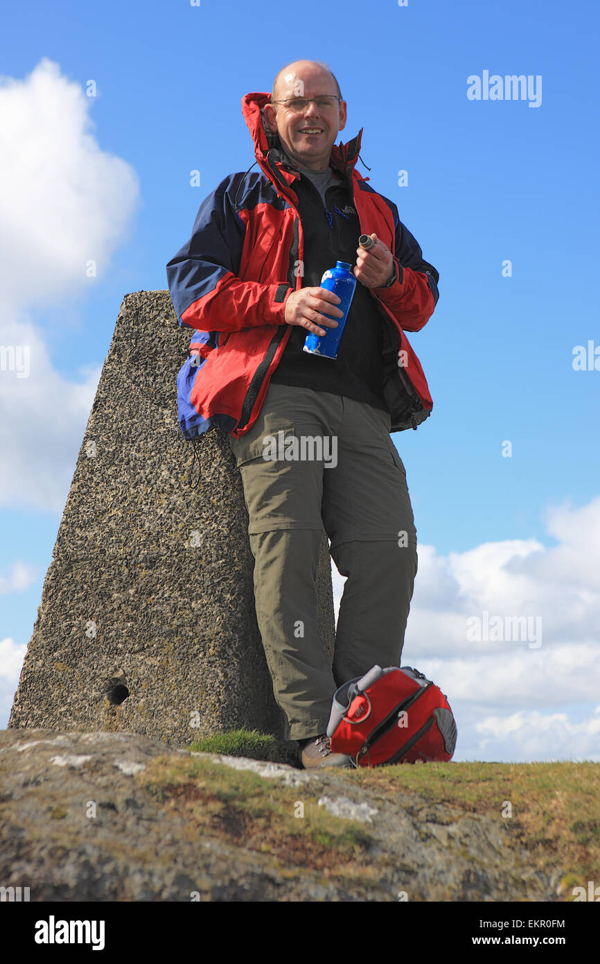 Man leaning on a trig point and about to take a drink of water at the summit of Knock Hill near Largs in Scotland - Stock Image