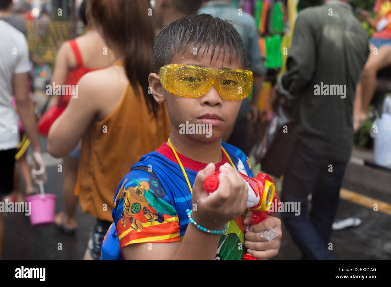 Bangkok, Thailand. 13th April, 2015. A young boys holds his water pistol in the annual Songkran festival on Silom - Stock Image