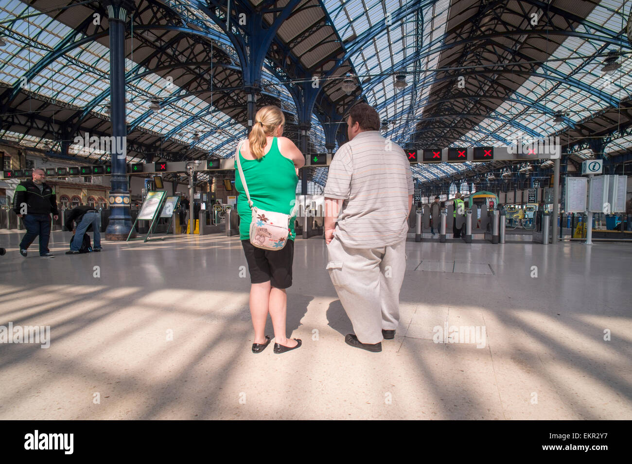 overweight couple standing on Brighton train Station concourse - Stock Image