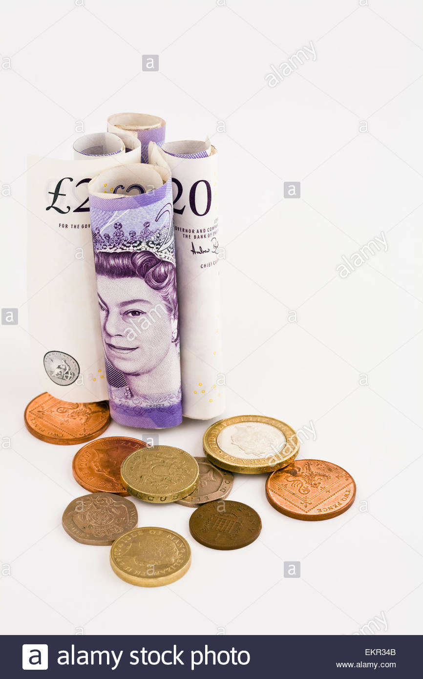 Rolled up 20 pound notes with coins on white background with copy space Stock Photo