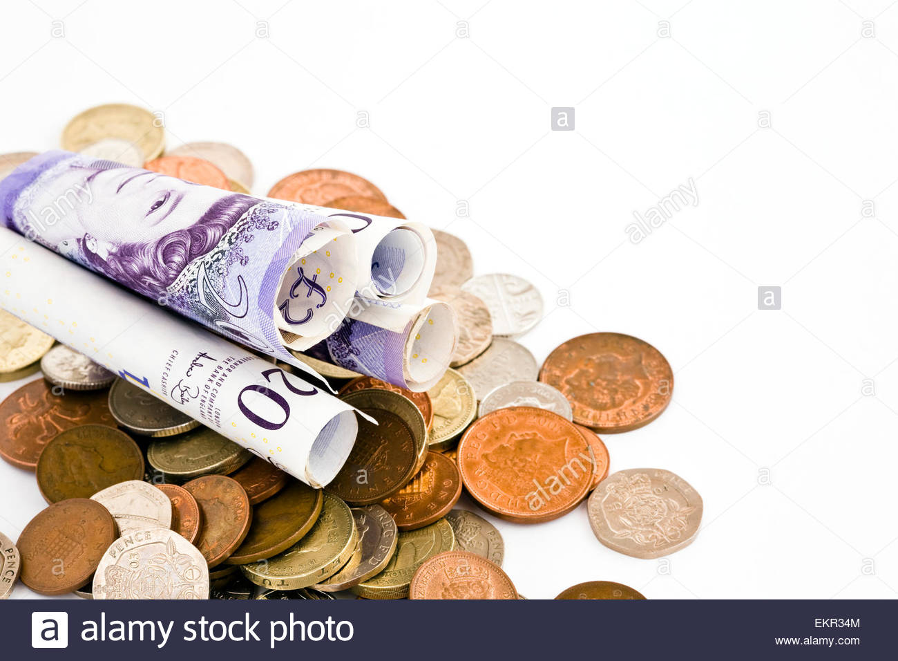 Rolled up 20 pound notes with coins on white background with copy space - Stock Image
