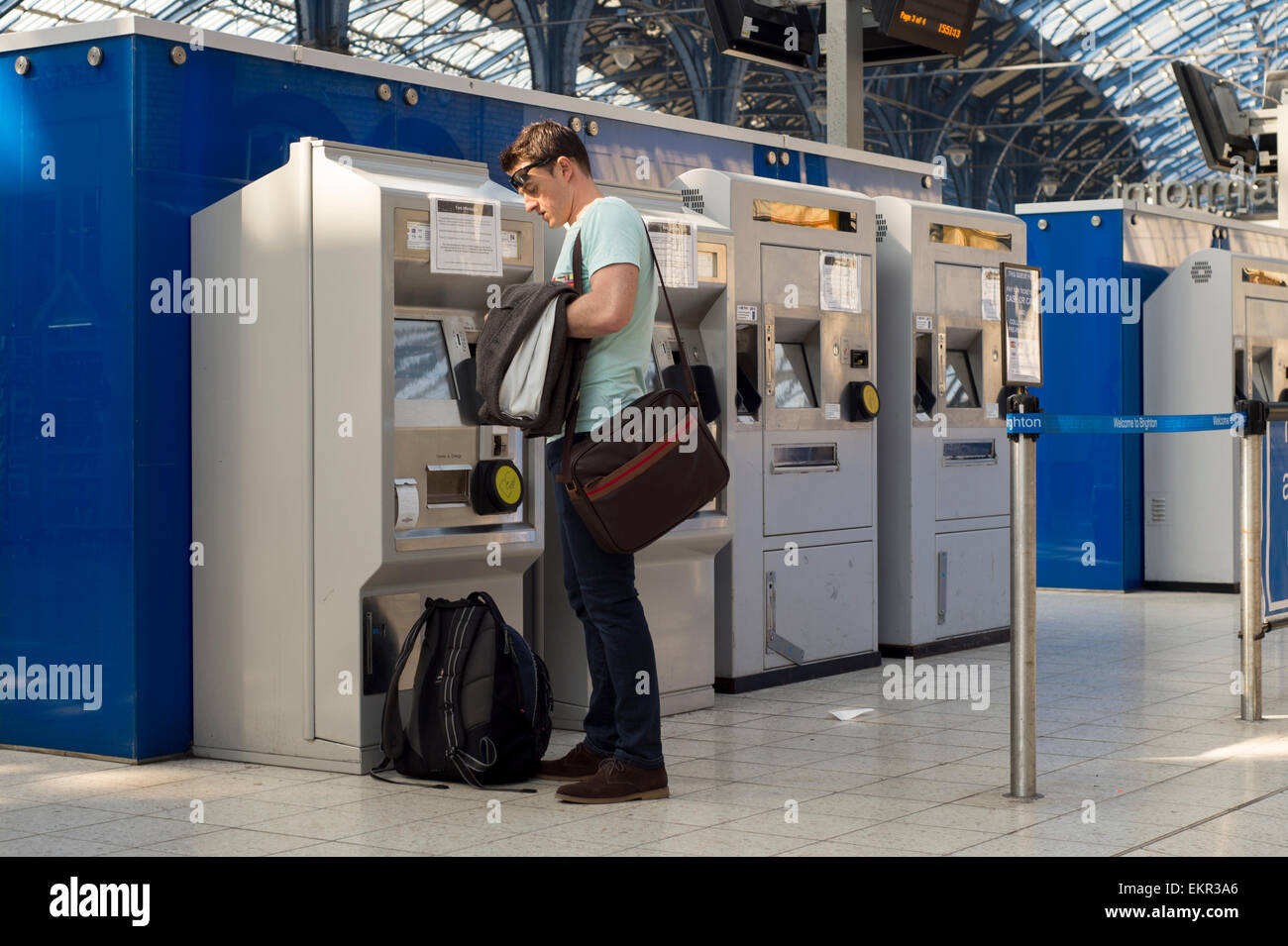 Commuter buying a rail ticket from a self service machine at Brighton Station - Stock Image