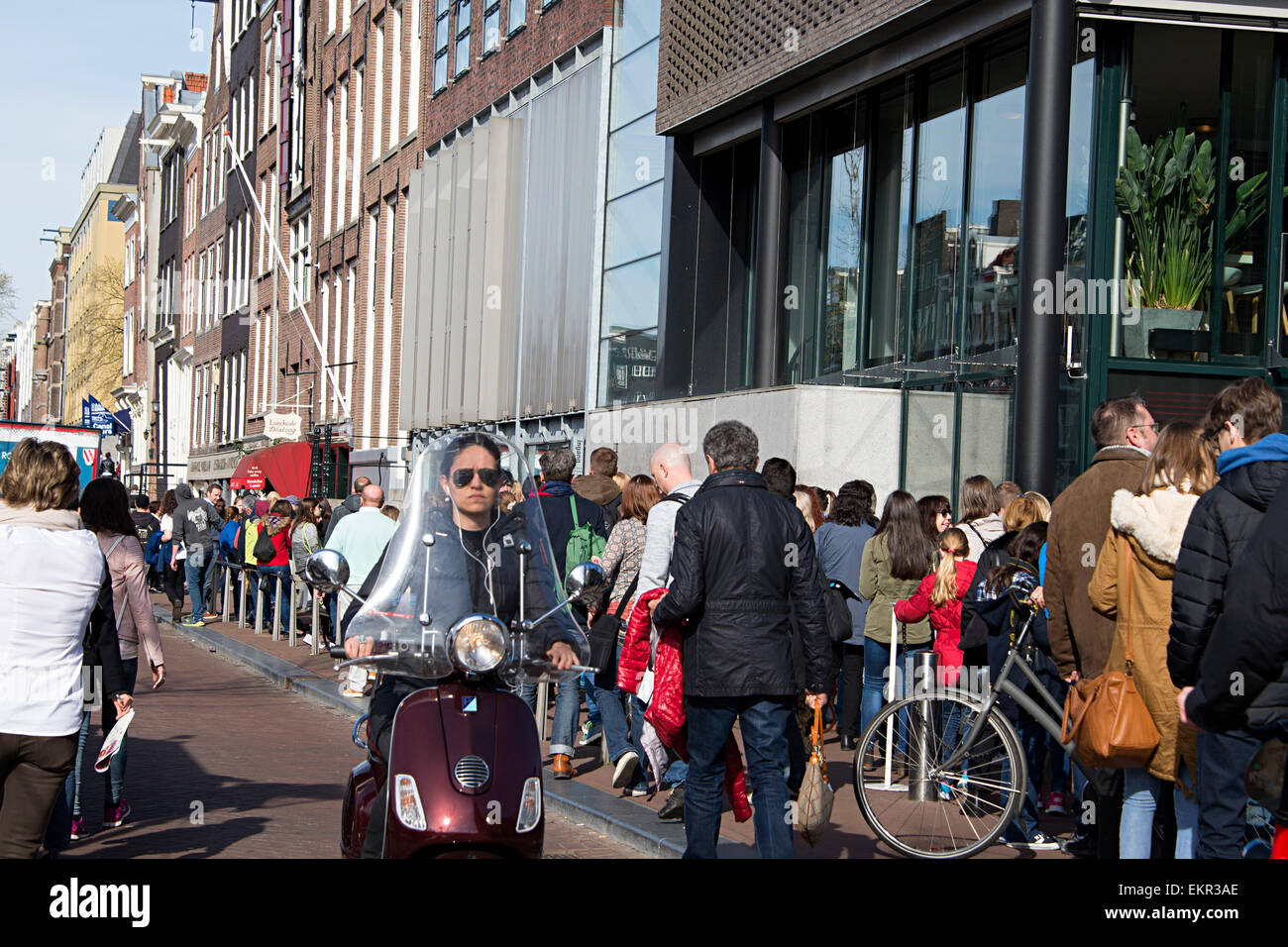 Long queues of people wait to go into the historic Anne Frank house. - Stock Image