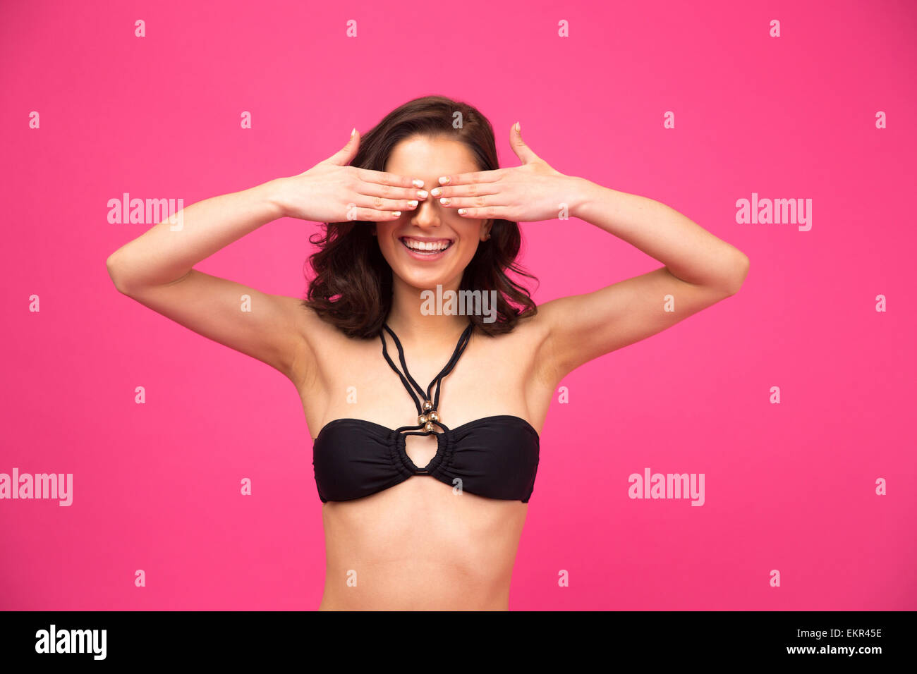 Happy young woman in black bikini covering her eyes over pink background - Stock Image