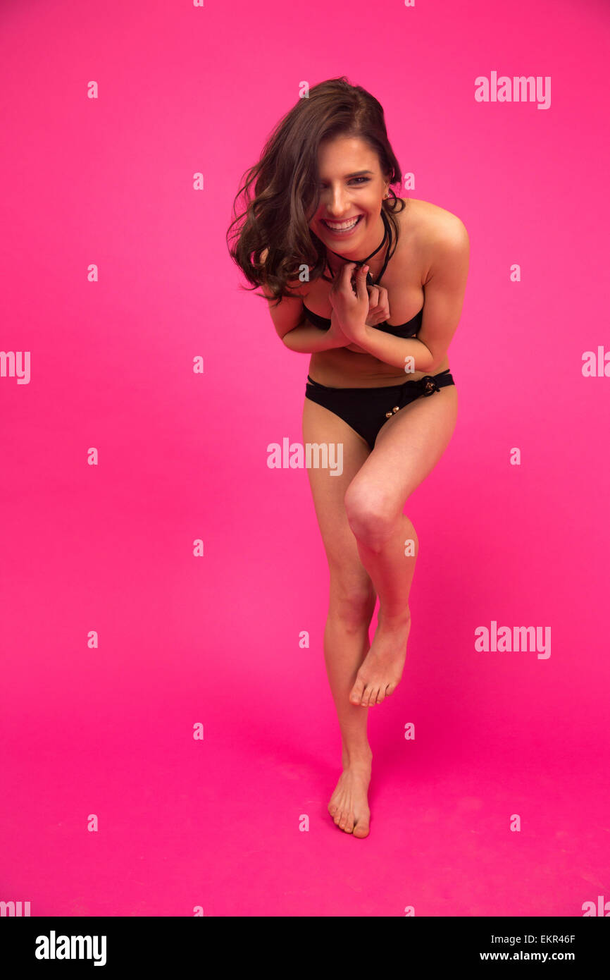 Full length portrait of a young funny woman posing in bikini over pink background. Looking at camera - Stock Image