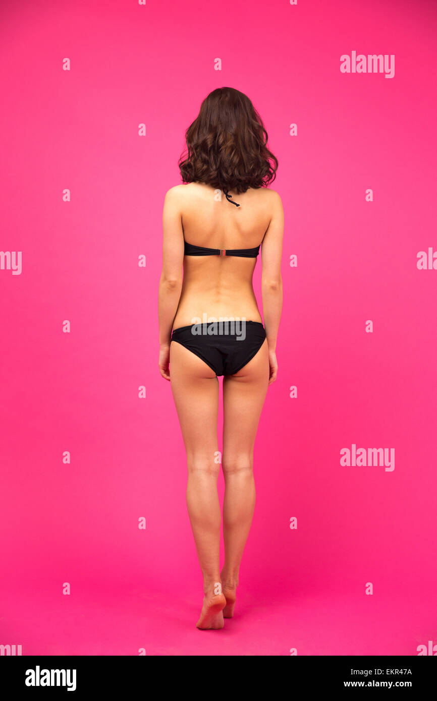 Back view portrait of a woman in bikini posing over gray background - Stock Image