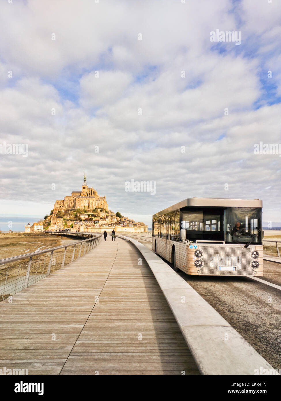 Mont Saint-Michel from the new causeway, with one of the shuttle buses which carry visitors to and from the island... - Stock Image