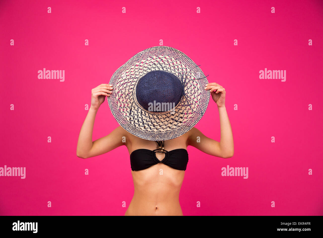 Woman in bikini covering her face with hat over pink background - Stock Image