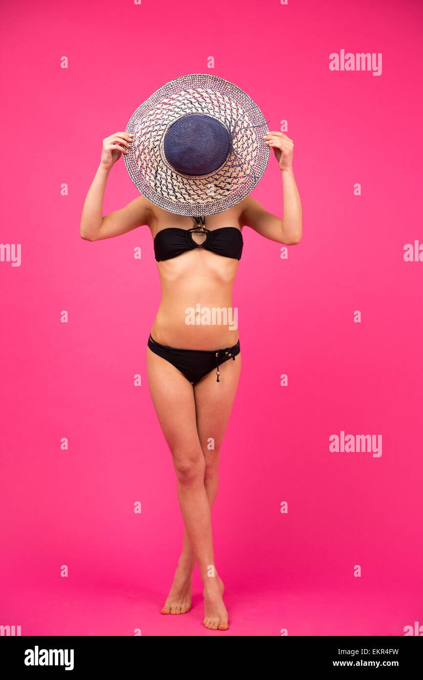 Full length portrait of a young woman in bikini covering her face with hat - Stock Image