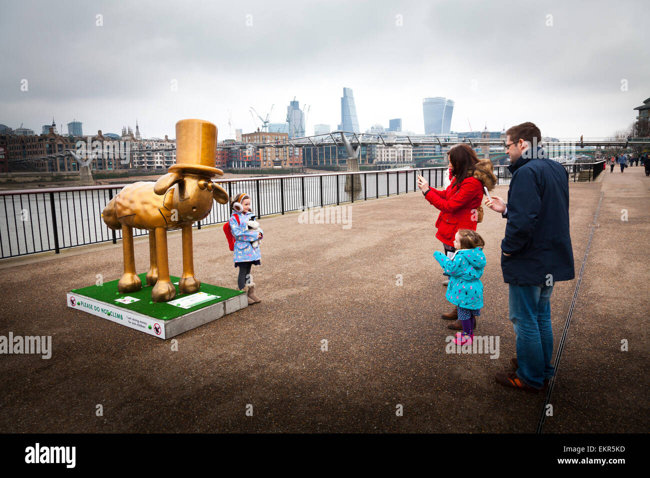 Parents photograph their child by one of the Shaun in the City sculptures by the thames in London - Stock Image