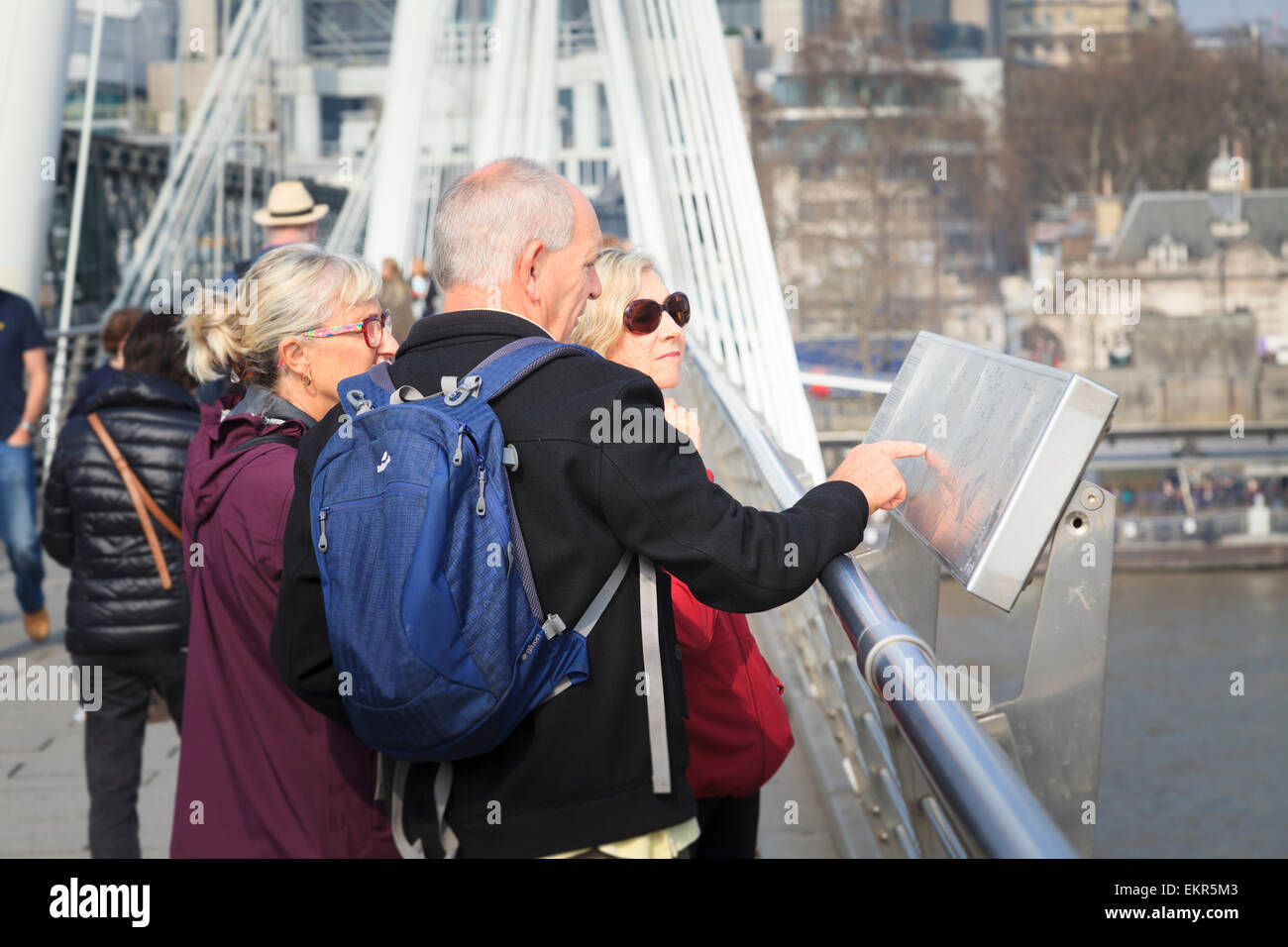 Tourists studying a landmark map on the Golden Jubilee Bridge over the Thames in London - Stock Image
