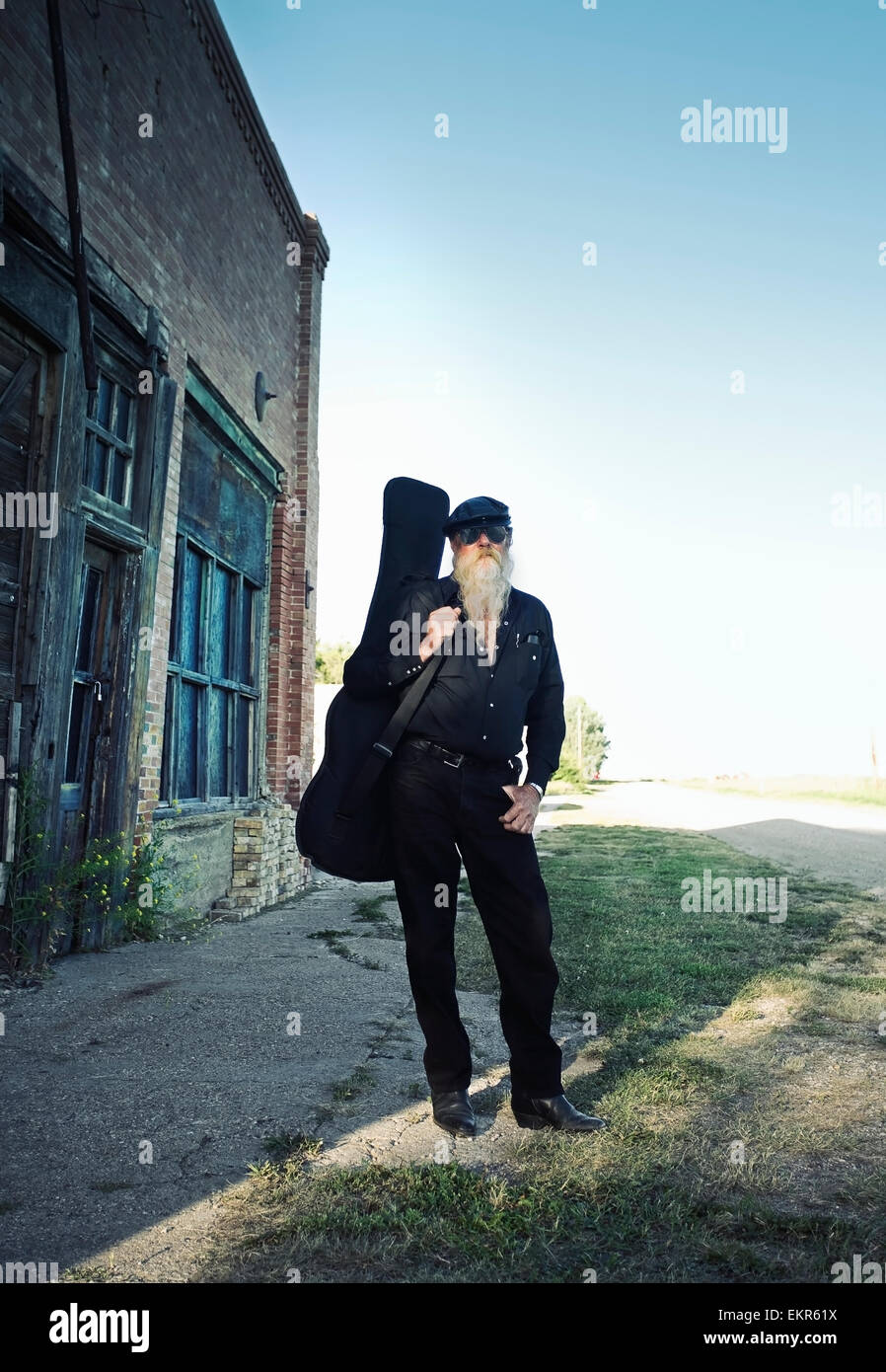 A man carrying a guitar. - Stock Image