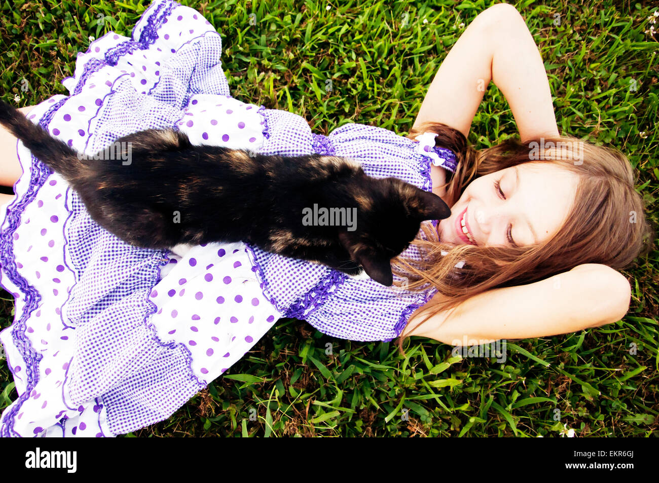 girl lying on grass with black calico cat - Stock Image