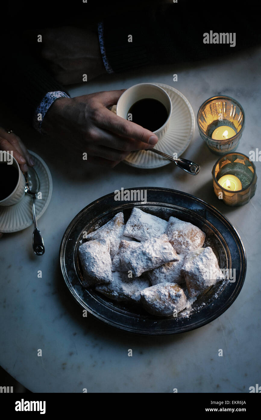 A man's hand on a cup of coffee. A tray of baked pastries. - Stock Image