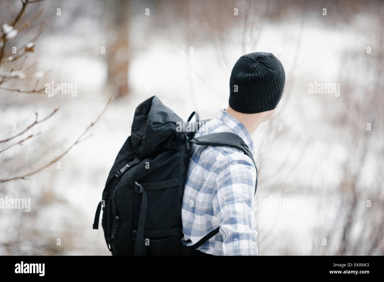 A hiker in the mountains with a rucksack and a woolly hat. - Stock Image