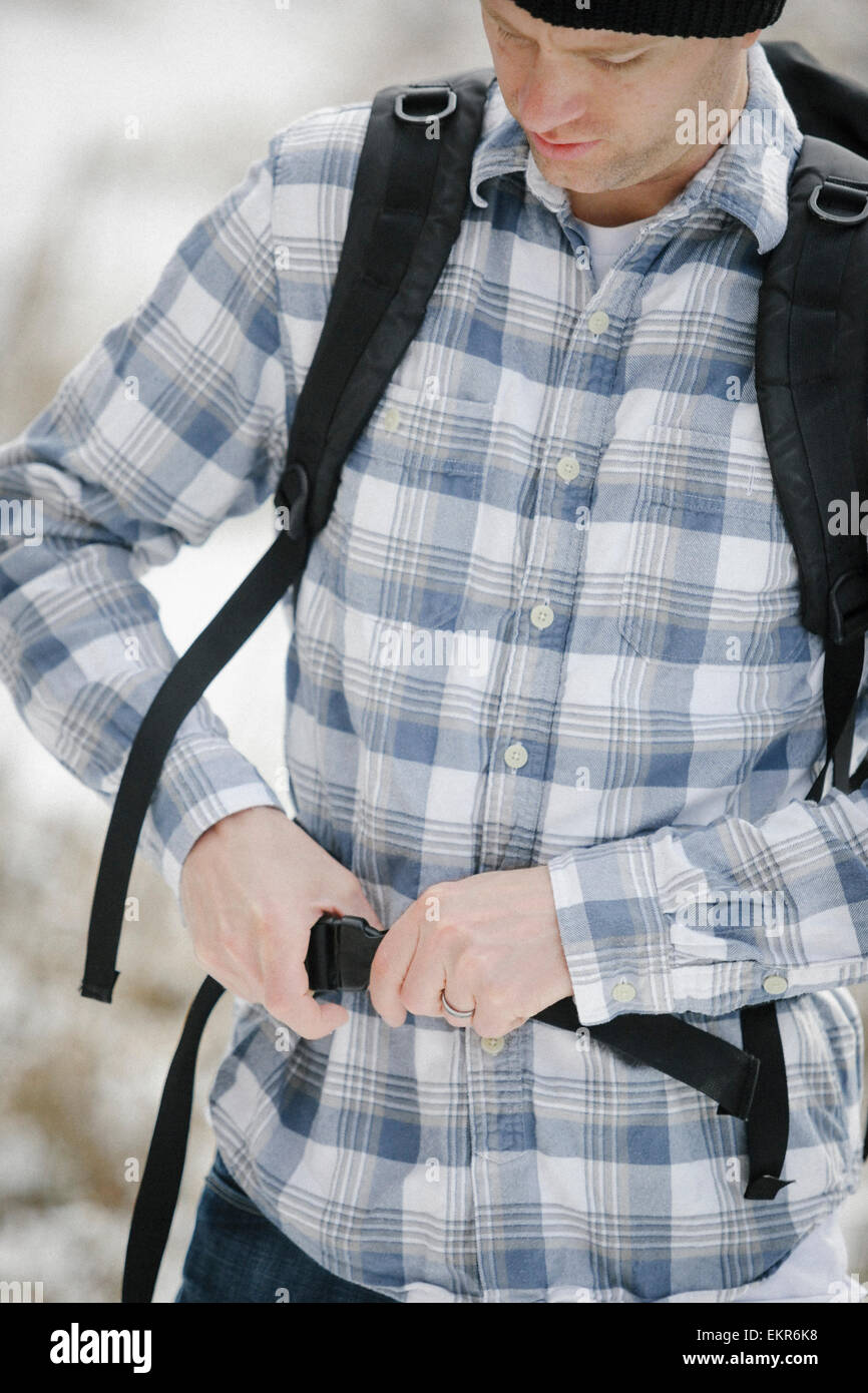 A man, a hiker fastening the belt securing his backpack. Stock Photo