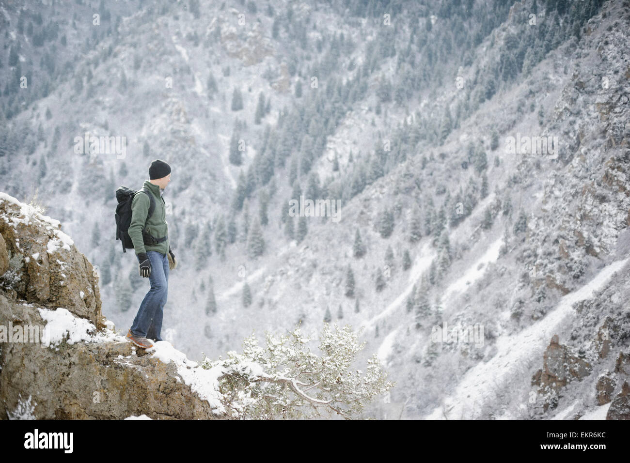 A man hiking in the mountains standing looking into a valley. - Stock Image