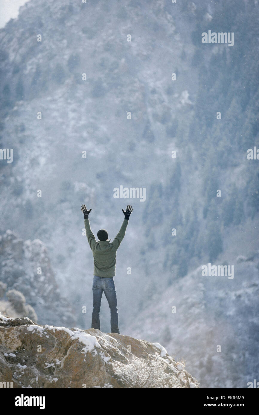 A man greeting the sun, with his arms raised on a rock outcrop in the mountains. - Stock Image