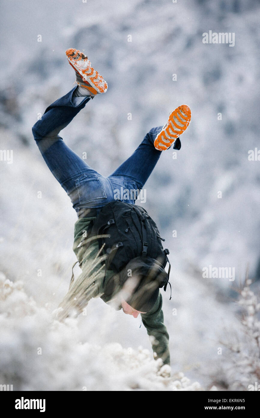 A hiker in the mountains with a rucksack, doing a handstand on a snowy slope. - Stock Image