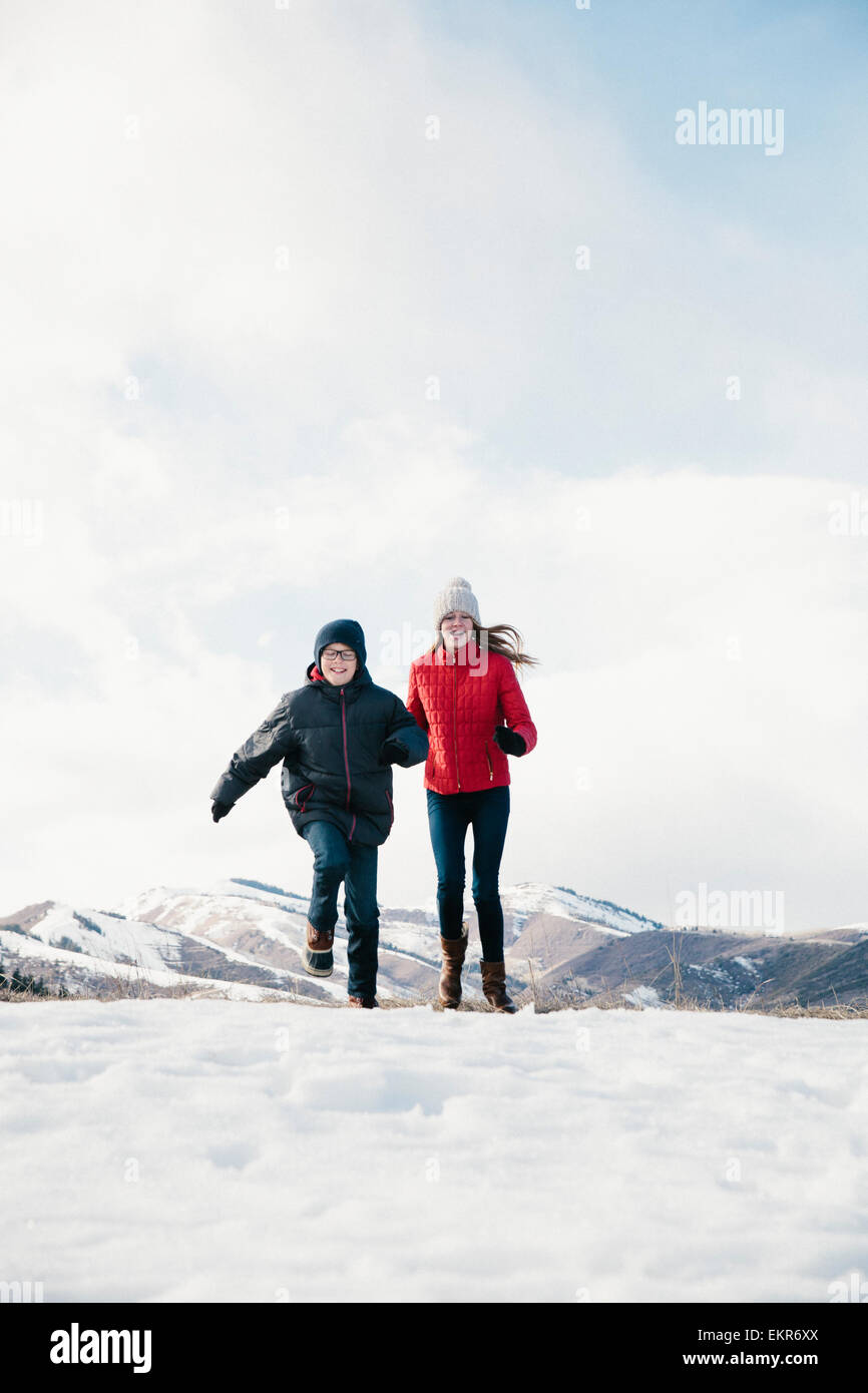 Two children, brother and sister running across the snow. Stock Photo