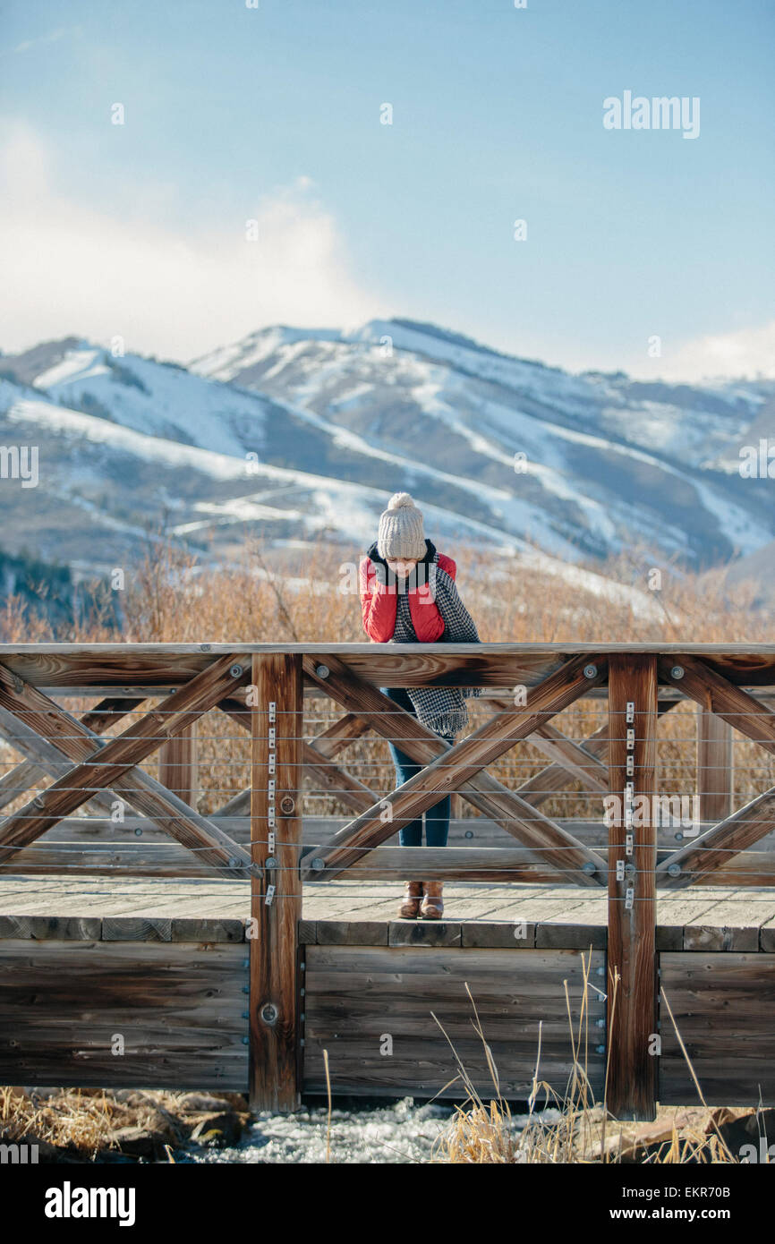 A girl in a red jacket with a woolly hat on leaning over the rail of a small footbridge. - Stock Image