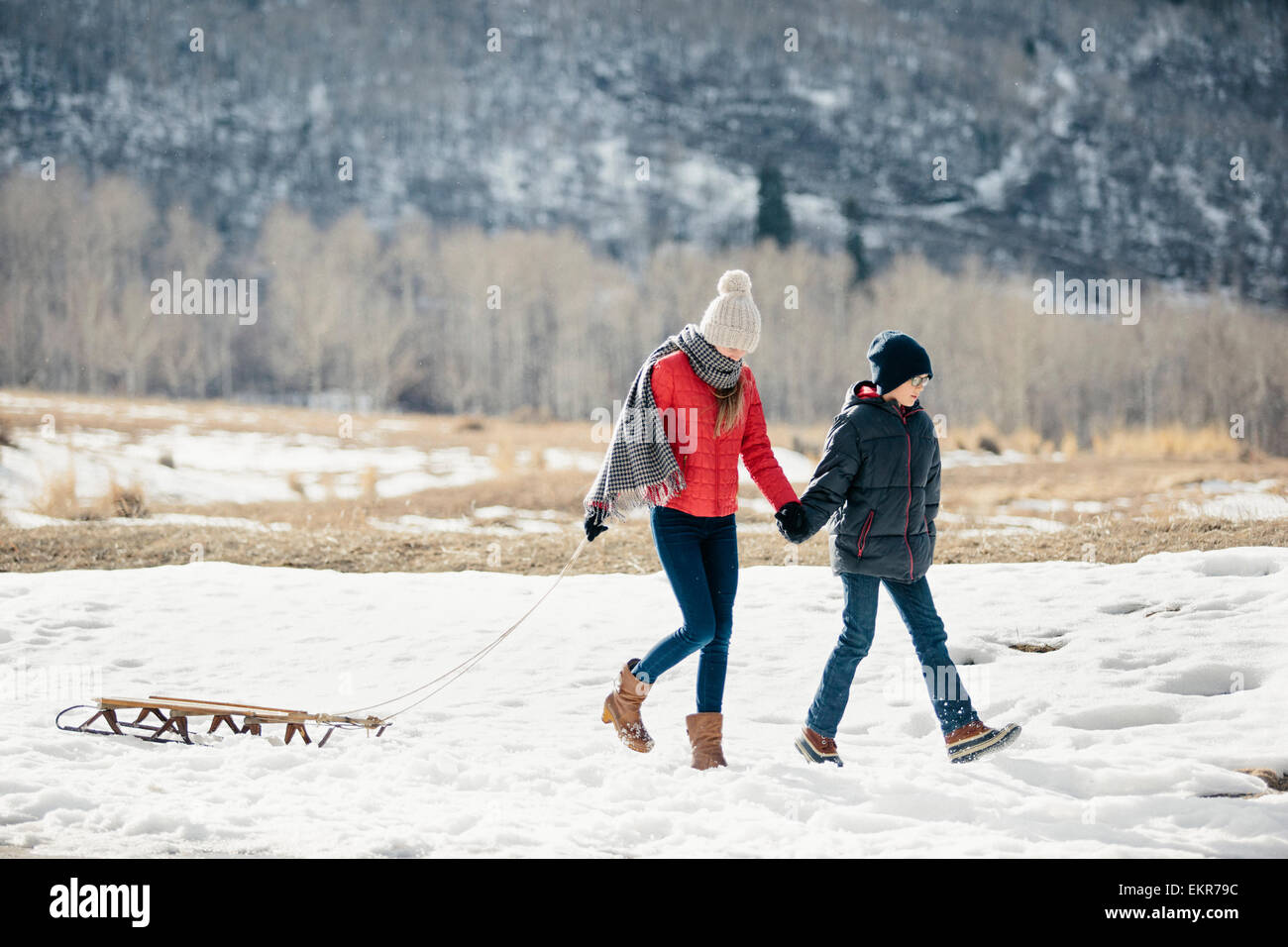A brother and sister in the snow, one pulling a sledge. Stock Photo