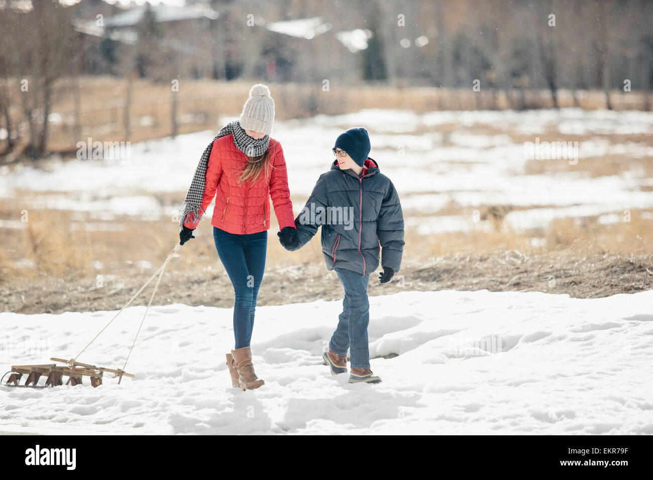 A brother and sister in the snow, one pulling a sledge. - Stock Image