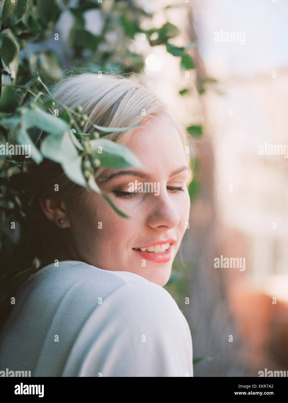 A pretty woman with a half smile, leaning against a vine growing up a wall. - Stock Image