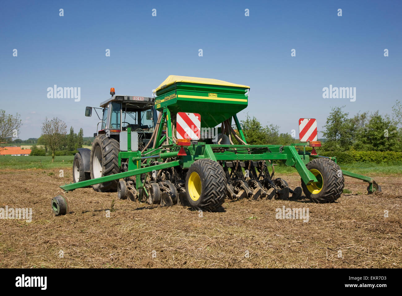 Tractor pulling John Deere 750A no-till seed drill working on farmland - Stock Image