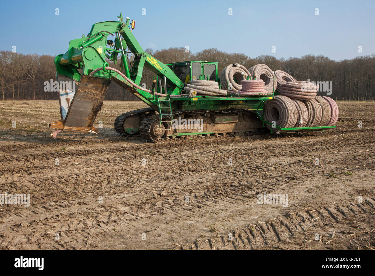 Drainage trencher / tile plow with load of drainage pipes working on farmland - Stock Image